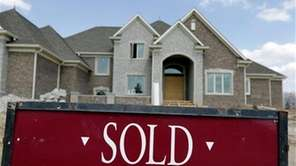 "A ""Sold"" sign is posted outside a home."