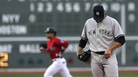 Yankees starting pitcher Andy Pettitte looks down as