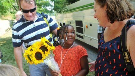 Ayahna, 7, of New York City, center, arrives