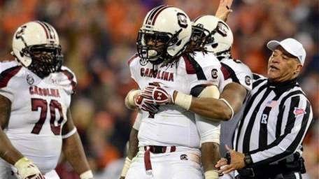 South Carolina's Jadeveon Clowney is hugged by a