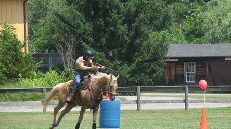 Jim Passarella Jr., riding Logan, aims his rifle