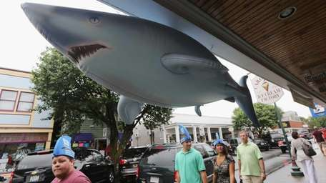 People wear shark hats during JawsFest: The Tribute,