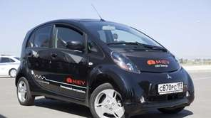 A 2012 Mitsubishi iMiEV is charged in Mineola.