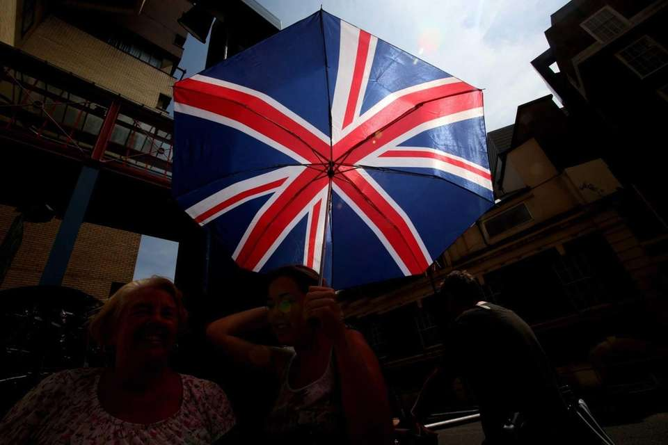 A woman holds a British flag umbrella outside