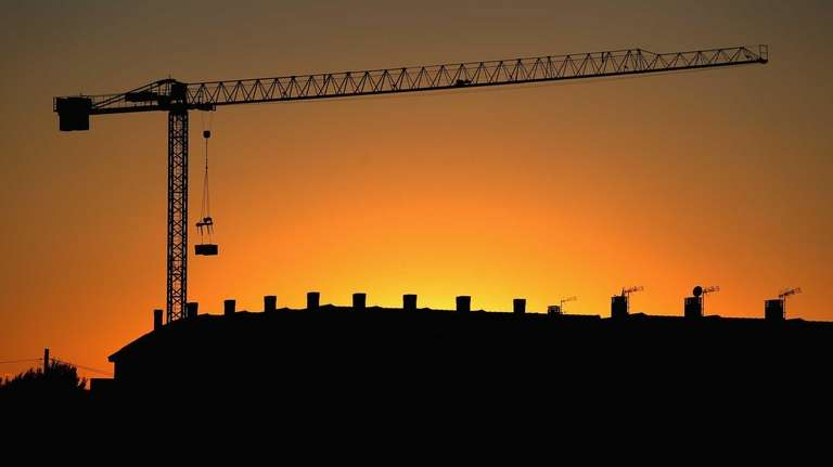 The sun sets behind a crane standing over