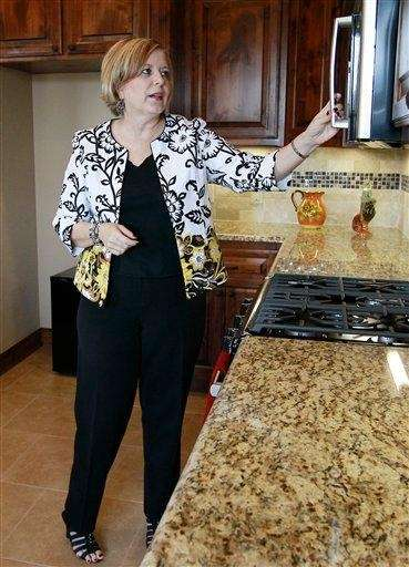Realtor Kimi George tours the kitchen of a