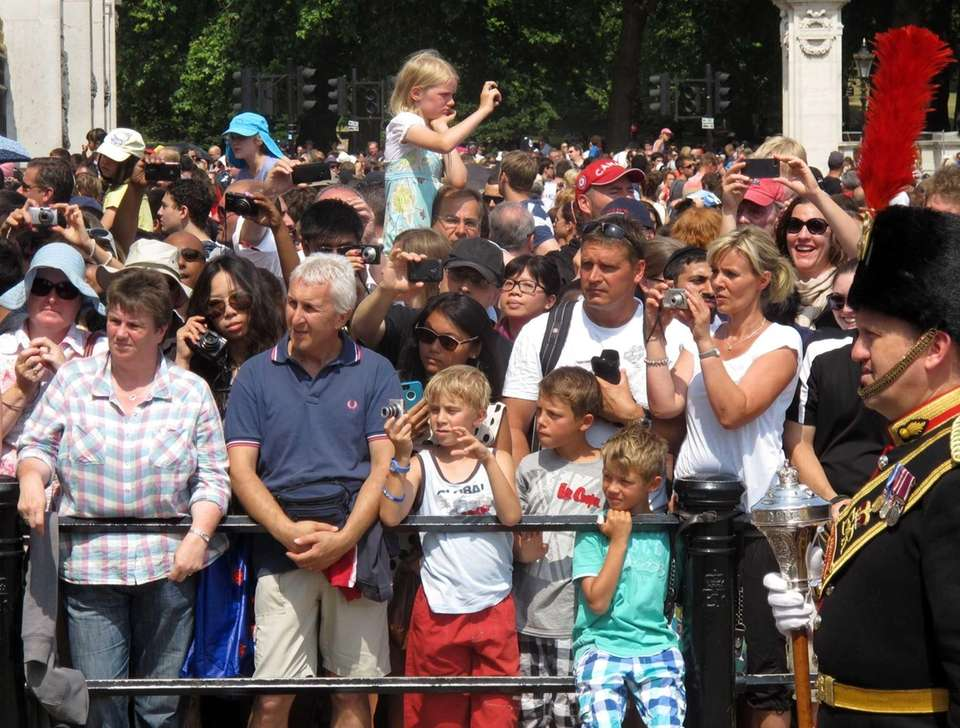 Spectators take photographs at Buckingham Palace. (July 22,