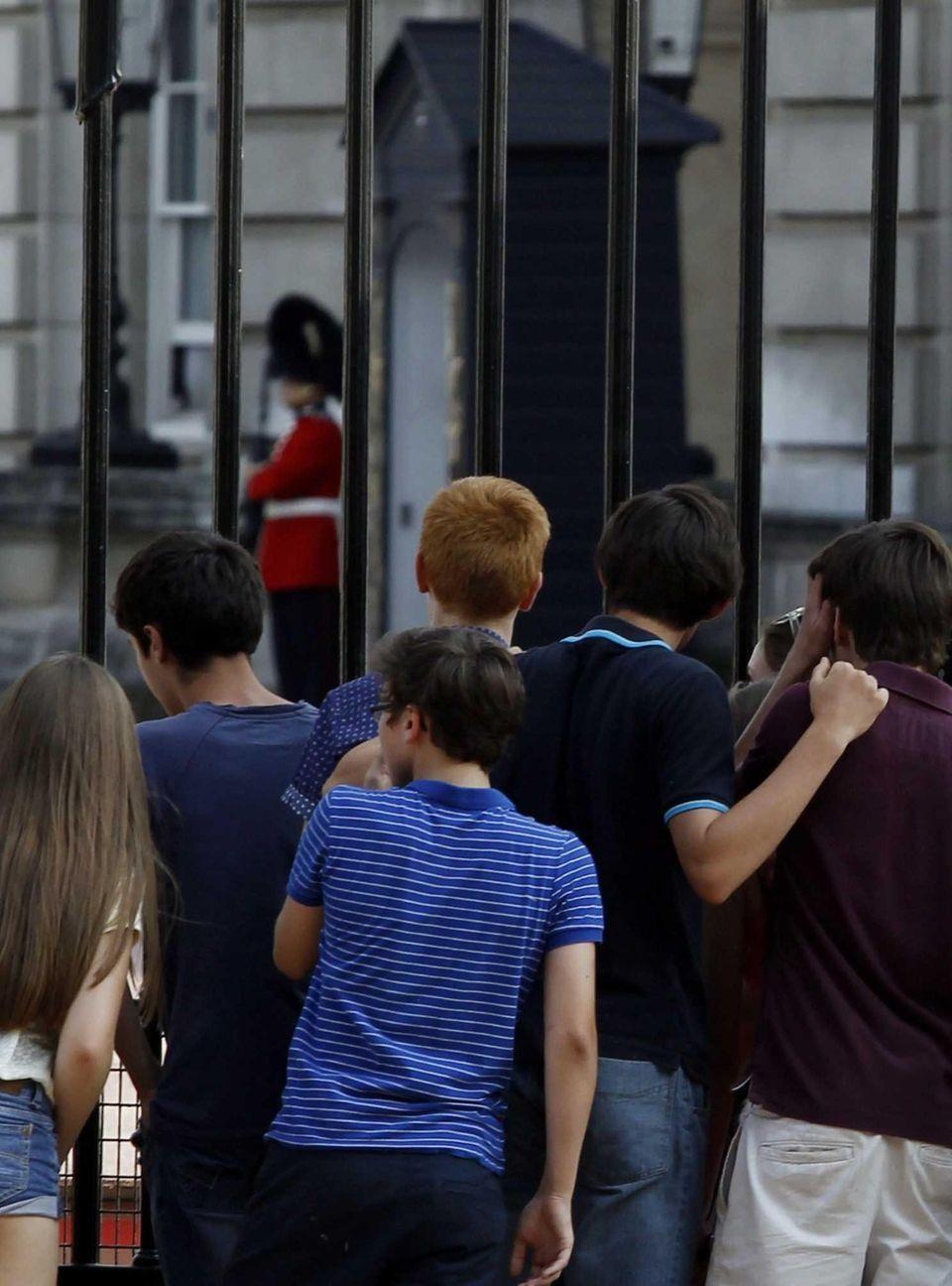 People wait outside of Buckingham Palace in London.