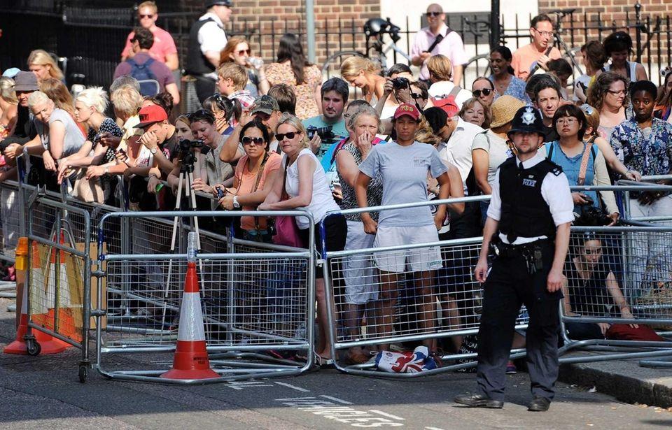 People wait outside St. Mary's hospital in London,