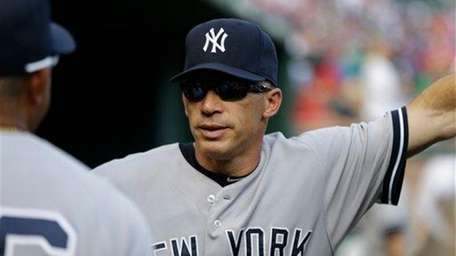 Joe Girardi stands in the dugout during the