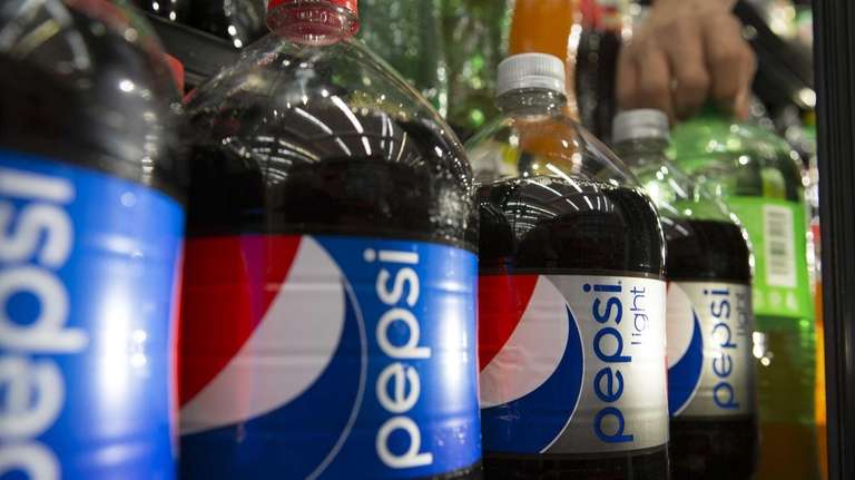 Bottles of PepsiCo Inc. soft drinks sit on