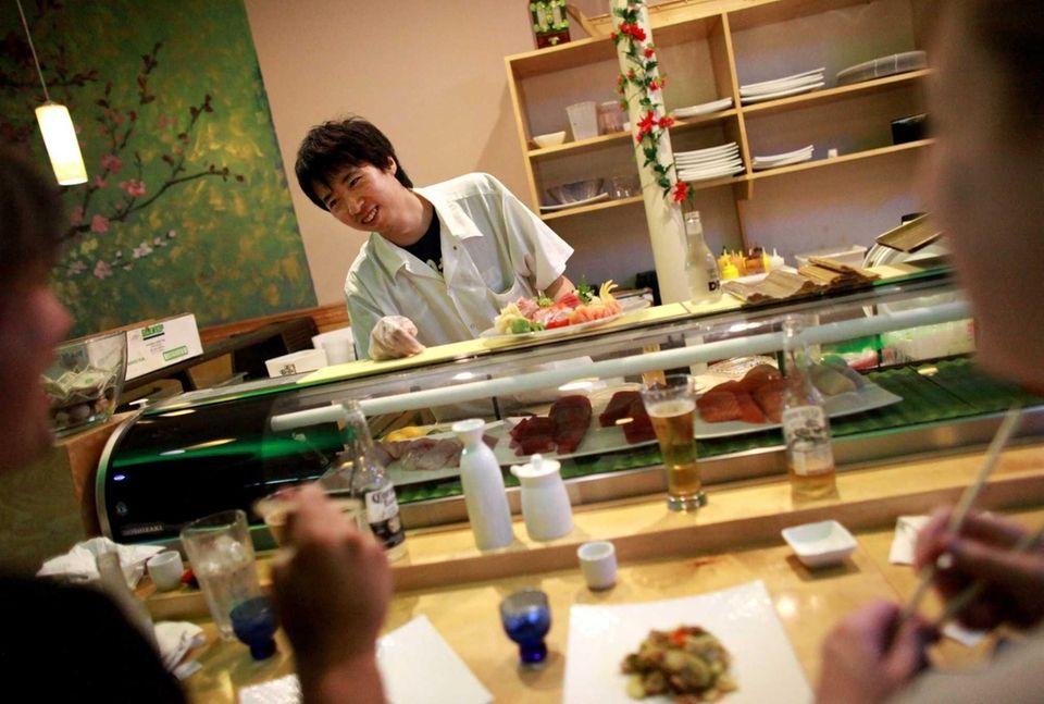 Sushi chef Kenny Liu prepares food at Sake