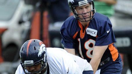 Denver Broncos quarterback Peyton Manning takes a snap