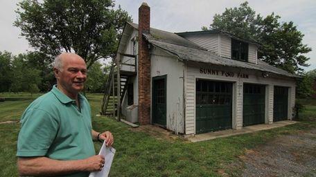 Tom Hogan stands near a garage in the