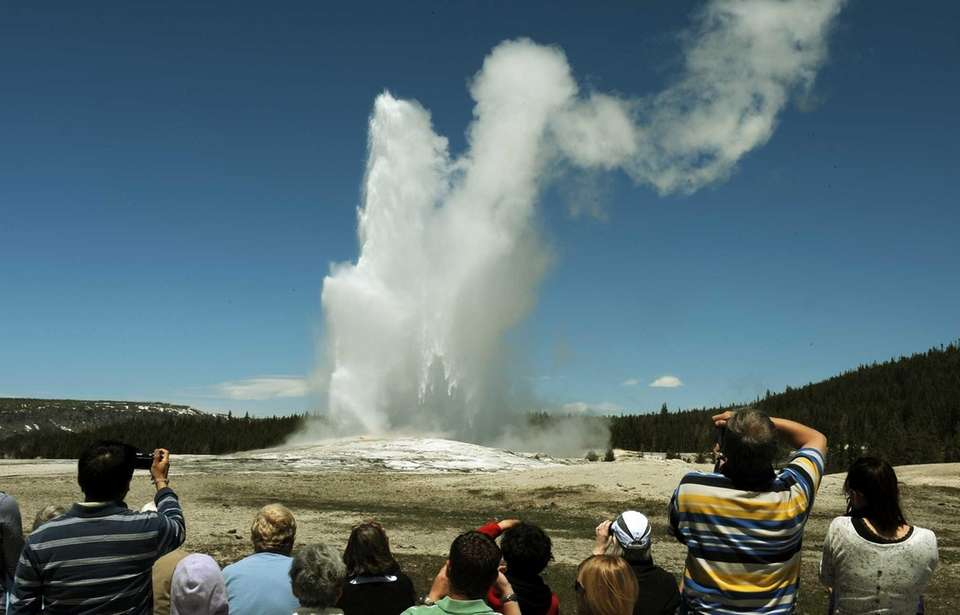 Tourists watch Old Faithful erupt, which the geyser