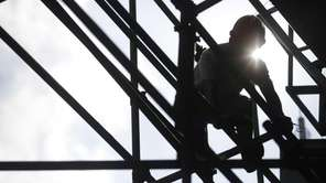 A construction worker sets up scaffolding in Shanghai,