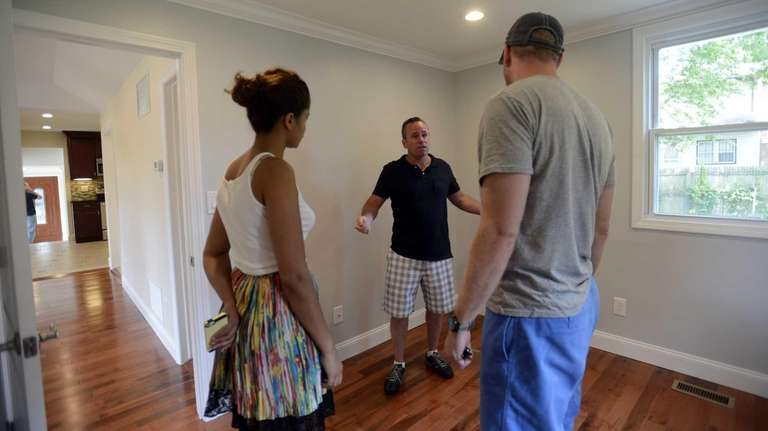 Real estate agent Edward Browne, center, shows a