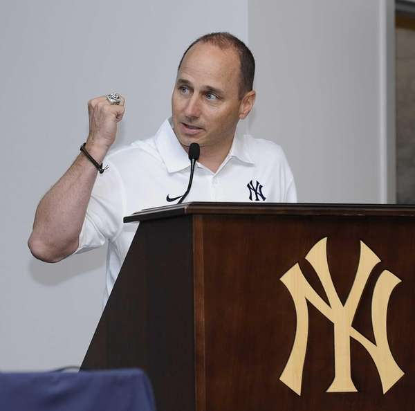 Brian Cashman holds up a championship ring at
