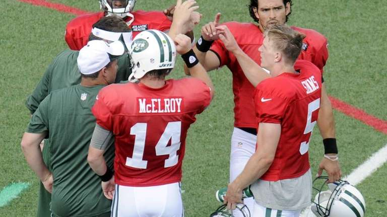 Jets quarterbacks and coaches huddle after a practice