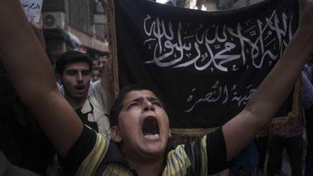 A Syrian boy shouts slogans against Bashar al-Assad
