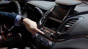 A representative from General Motors opens a compartment