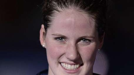 Missy Franklin smiles as she holds the gold