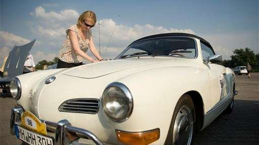 A woman inspects a classic Karmann Ghia car.