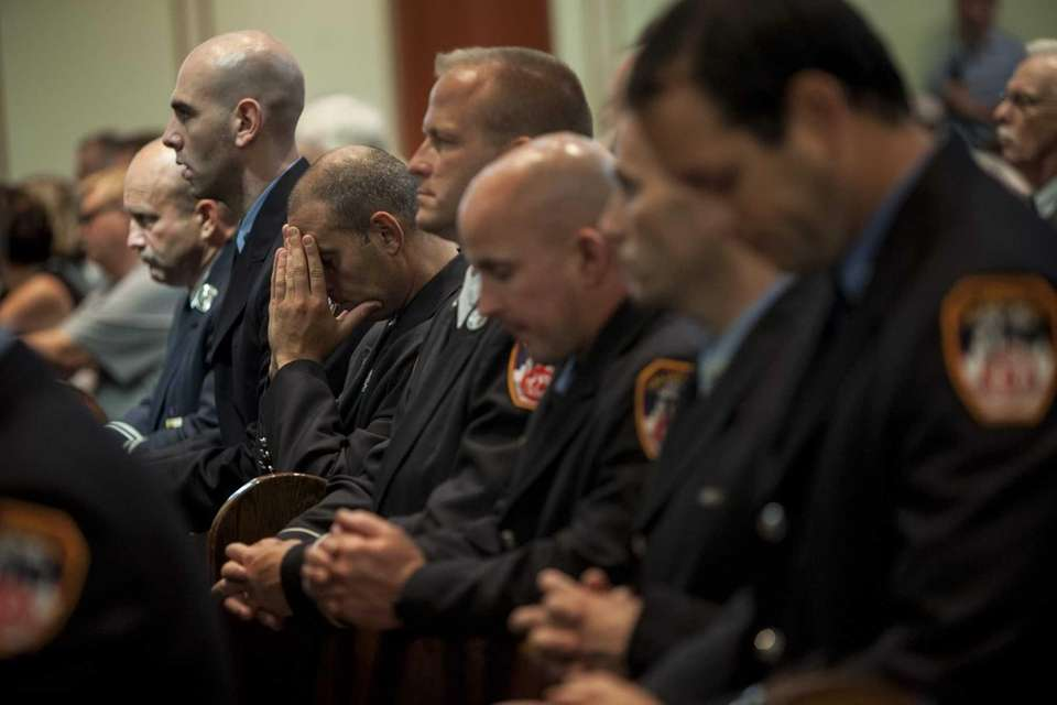FDNY members pause at a memorial service at