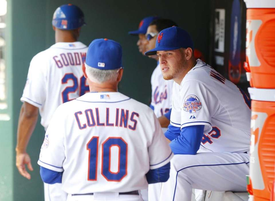 Mets pitcher Zack Wheeler, right, sits in the