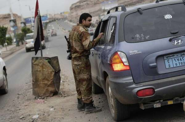 A Yemeni soldier inspects a car at a