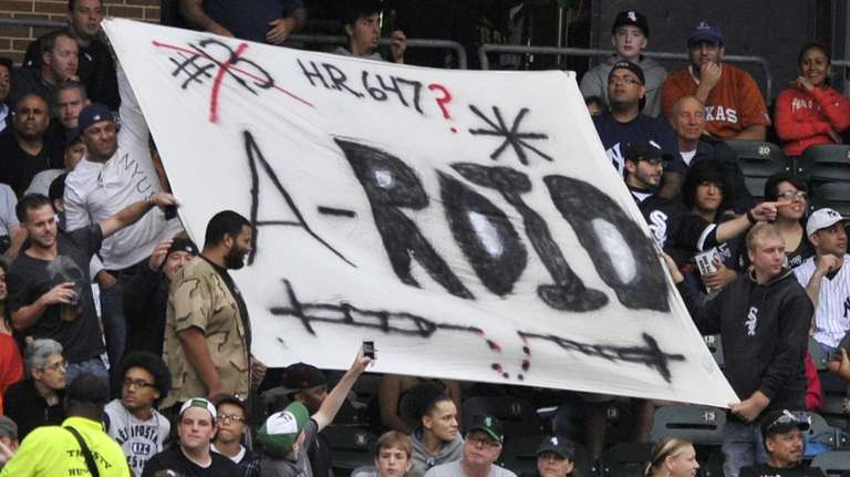 Fans hold a sign made for Alex Rodriguez