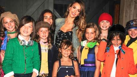 Actress Jessica Alba poses with some of the