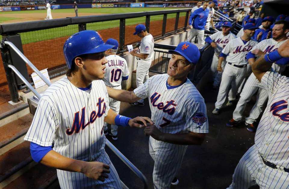 Wilmer Flores celebrates in the dugout after scoring