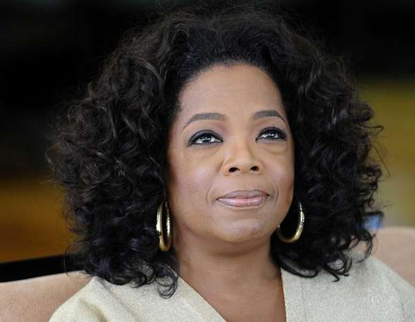 Oprah Winfrey looks on as she answers journalist's