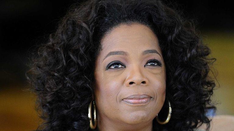 Oprah Winfrey looks on as she answers journalist's