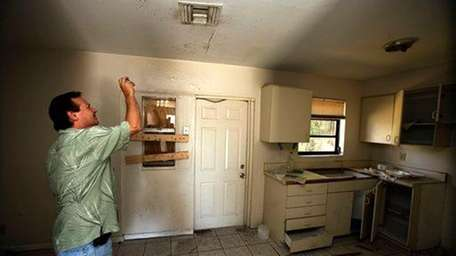 Frank Verna takes photos of a kitchen ceiling