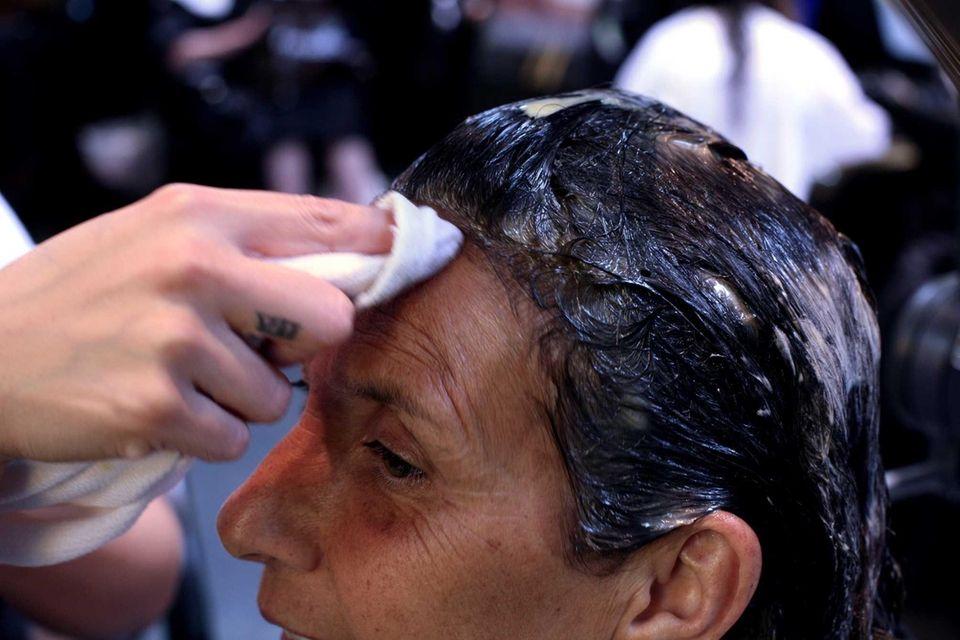 A stylist applies dye to Linda Beyer's hair.