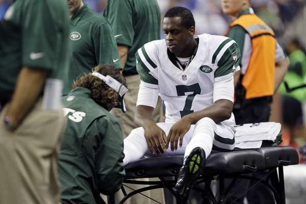 Jets quarterback Geno Smith (7) is examined during
