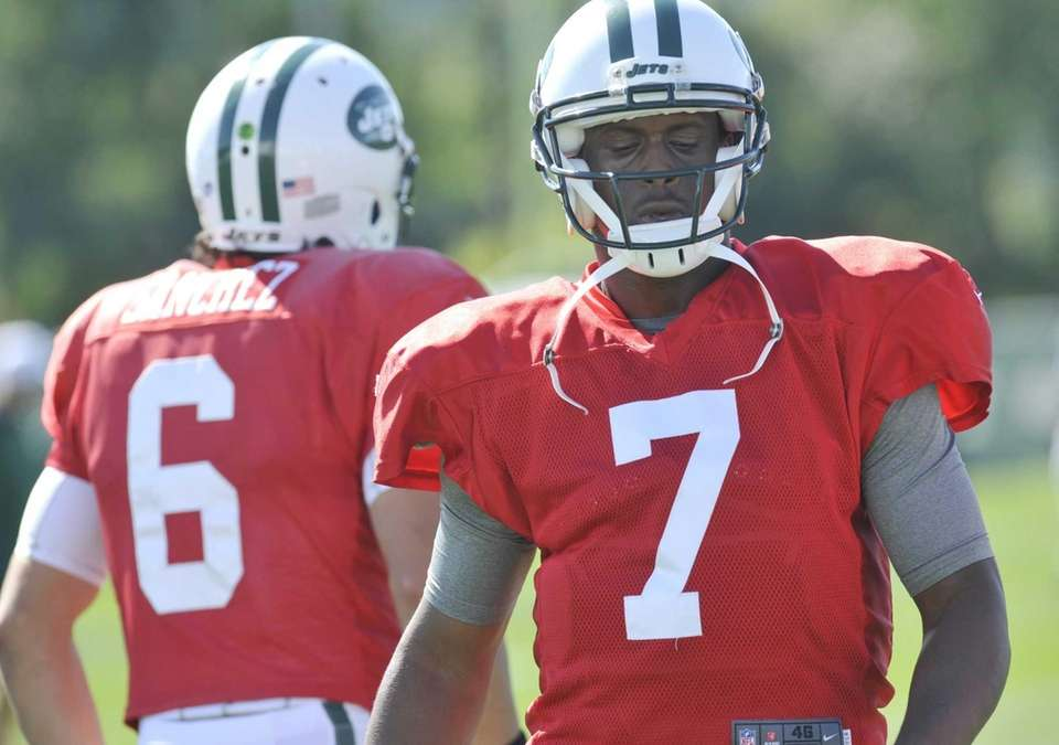 Jets quarterback Geno Smith, right, walks past quarterback
