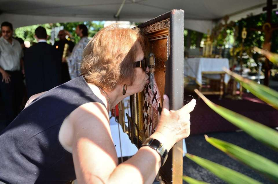 Athena Mountanos of Bellmore kisses a damaged painting