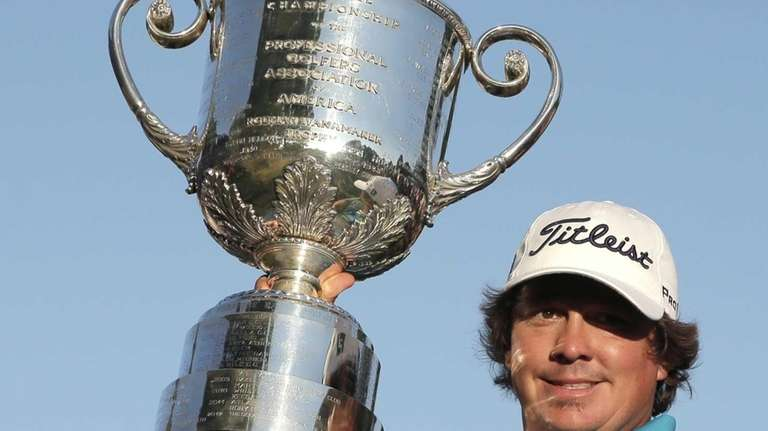 Jason Dufner holds up the Wanamaker Trophy after