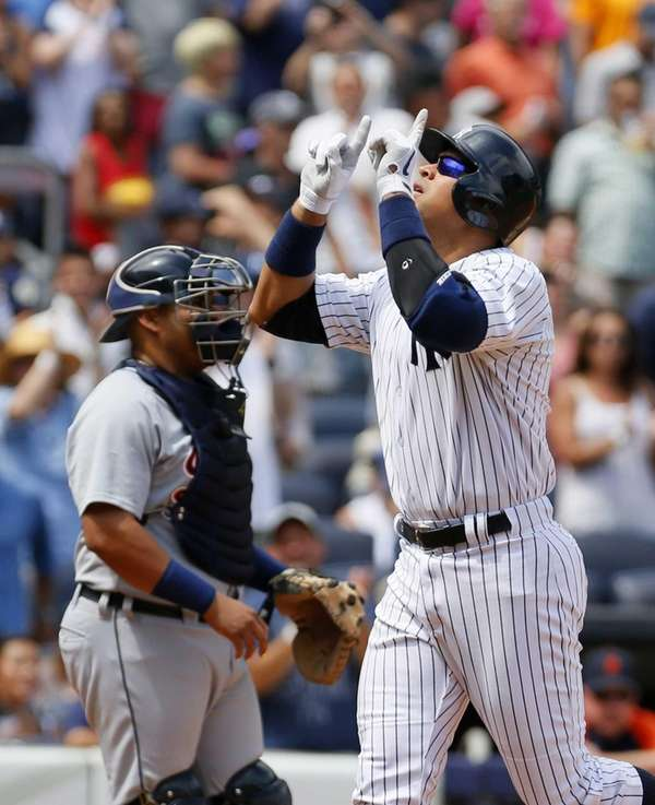 Alex Rodriguez points to the sky after hitting