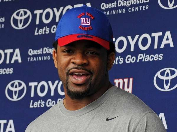 Giants defensive end Damontre Moore speaks with the