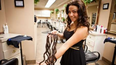 Nicole Espinal holds hair extensions that she used