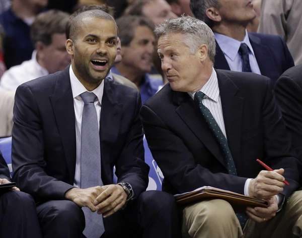 San Antonio Spurs guard Tony Parker, left, sits