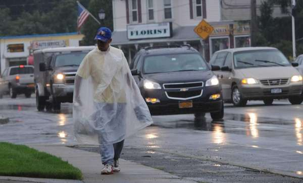 A man uses a poncho to keep dry