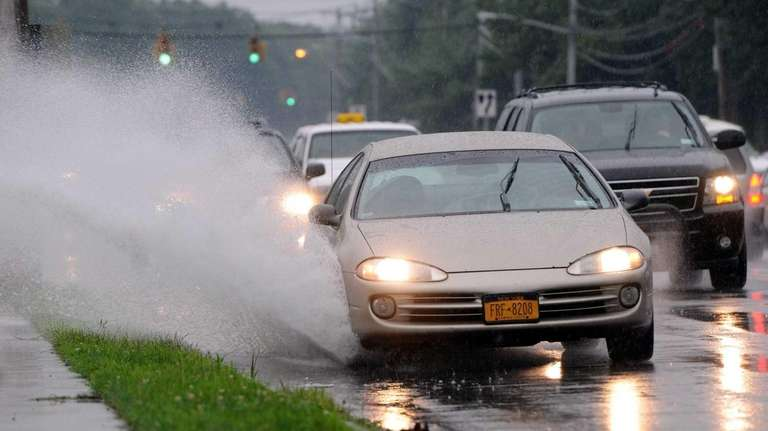 A vehicle splashes through a large puddle on