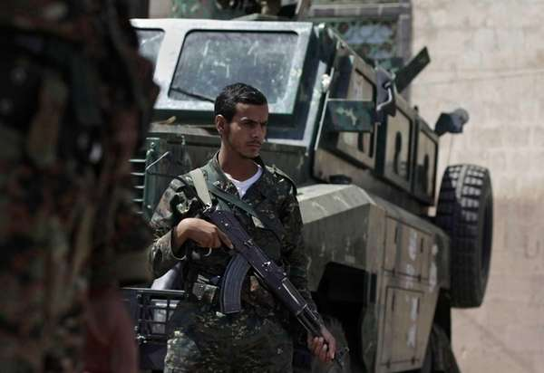 Yemeni soldiers man a checkpoint on a street