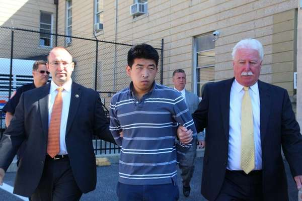 Renhang Qiu, 22, of Brooklyn, has been charged with burglary, attempted robbery and criminal possession of a weapon, in connection with a home invasion and shooting of Officer Mohit Arora in North New Hyde Park, police said. Qiu leaves Nassau police headquarters in Mineola to be arraigned. (Aug. 15, 2013)