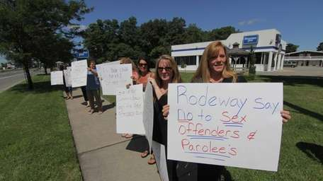 Protesters carry signs if front of Rodeway Inn
